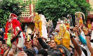 A crowd of Santa Muerte followers holding up yellow, white, and black Santa Muerte statues.